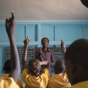 Elever rækker hænderne op for at svare på lærerens spørgsmål