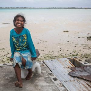 Teretia på 8 år sidder på et toilet nær hendes hjem i landsbyen Bikenibeu i det sydlige Tarawa