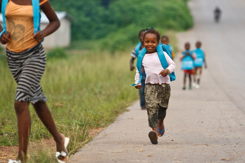 Børn løber til skole med UNICEF skoletasker på ryggen. Et af UNICEF Danmarks børnemål er at sikre at yderligere 750.000 børn får adgang til undervisning og skolegang.