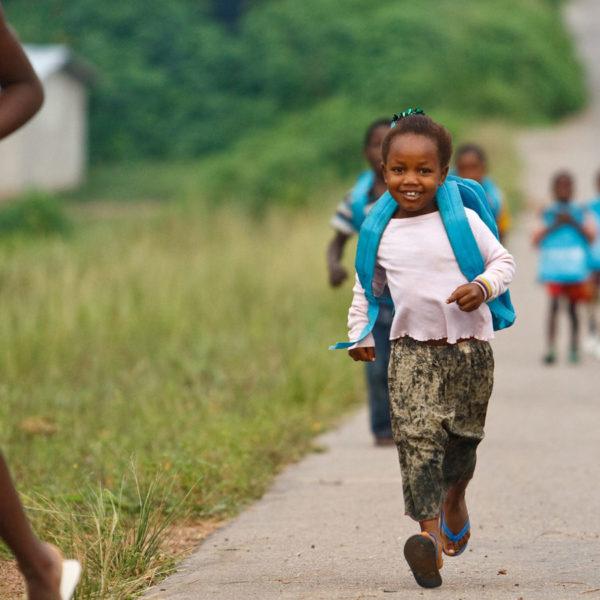 En flok skolebørn kommer løbende til skole med UNICEFs skoletasker på ryggen i Bloleu landsbyen i Elfenbenskysten.