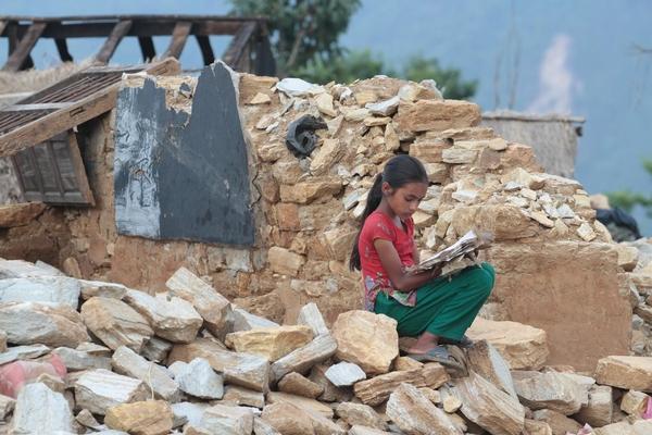 En pige sidder mellem murbrokkerne i Gorkha, som er et af de områder, der blev hårdt ramt af jordskælv i 2015.