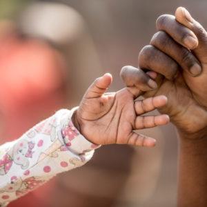 19-årige Martha fra Malawi rækker ud efter sin lille søns hånd, 8 måneder gamle Rahim Idriss.