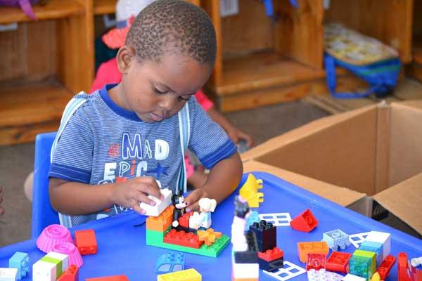 Et 3-årigt barn fra Diepsloot Pre-School i Sydafrika leger med LEGO klodser.