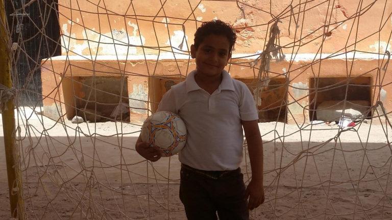 En flygtninge dreng fra Yemen står med fodbold