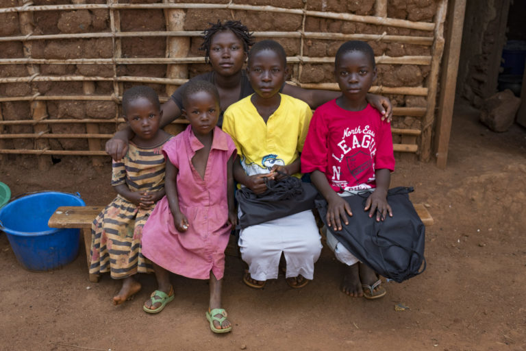 "On 15 September 2018, Stephanie,10, (wearing the red shirt) sits with her older sister Prefna (wearing black shirt) and her other siblings at their home in Mangina in the Democratic Republic of Congo. Stephanie's mother mother was killed in crossfire in a gun battle two years ago in Beni in the Democratic Republic of Congo. Stephanie and her sisters were then sent to live with an aunt in Mangina. Last month, the aunt contracted Ebola and died, leaving the girls orphaned. The oldest sister, Prefna, now 18, has stepped up, acting as mother, father, sister and fierce defender. UNICEF is helping children like Stephanie by giving food, material assistance, and psycho-social care, as well as providing school supplies so they can quickly return to the classroom. Stephanie says she's excited. ""I will go to school Monday because I was given a uniform, a school bag, pens, pencils and a sharpener."" In September 2018 UNICEF and its partners have so far identified 155 children who have been orphaned or left unaccompanied as a result of the latest Ebola outbreak in the eastern Democratic Republic of the Congo (DRC). This figure includes children who have lost one or both parents, or primary caregivers to Ebola, as well as those who have been left unaccompanied while their parents are isolated in Ebola treatment centres. UNICEF assistance to orphaned and unaccompanied children is tailored to meet the specific needs of the individual child. A new-born who has lost his mother has different needs than a school-aged child. UNICEF support to an orphaned or unaccompanied child typically includes psycho-social care, food and material assistance, and support to reintegrate into school."