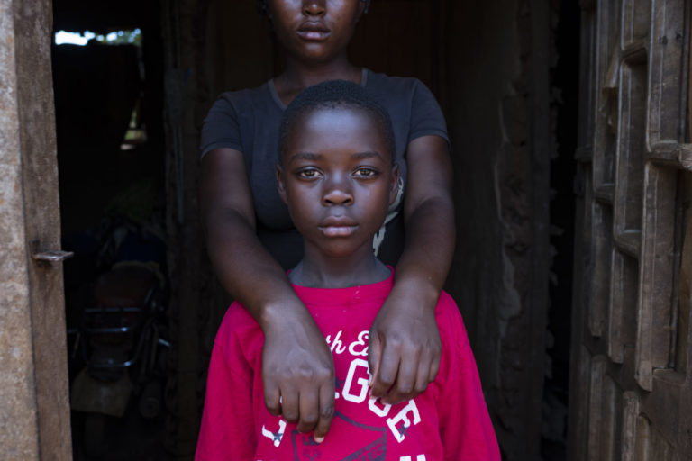 "On 15 September 2018, Stephanie,10, (wearing the red shirt) with her older sister Prefna (wearing black shirt) at their home in Mangina in the Democratic Republic of Congo. Stephanie's mother mother was killed in crossfire in a gun battle two years ago in Beni in the Democratic Republic of Congo. Stephanie and her sisters were then sent to live with an aunt in Mangina. Last month, the aunt contracted Ebola and died, leaving the girls orphaned. The oldest sister, Prefna, now 18, has stepped up, acting as mother, father, sister and fierce defender. UNICEF is helping children like Stephanie by giving food, material assistance, and psycho-social care, as well as providing school supplies so they can quickly return to the classroom. Stephanie says she's excited. ""I will go to school Monday because I was given a uniform, a school bag, pens, pencils and a sharpener."" In September 2018 UNICEF and its partners have so far identified 155 children who have been orphaned or left unaccompanied as a result of the latest Ebola outbreak in the eastern Democratic Republic of the Congo (DRC). This figure includes children who have lost one or both parents, or primary caregivers to Ebola, as well as those who have been left unaccompanied while their parents are isolated in Ebola treatment centres. UNICEF assistance to orphaned and unaccompanied children is tailored to meet the specific needs of the individual child. A new-born who has lost his mother has different needs than a school-aged child. UNICEF support to an orphaned or unaccompanied child typically includes psycho-social care, food and material assistance, and support to reintegrate into school."