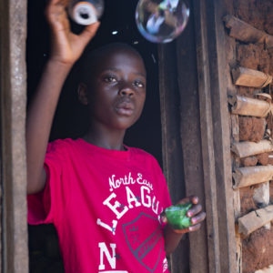 """On 15 September 2018, Stephanie makes soap bubbles at her home in Mangina in the Democratic Republic of Congo. Stephanie's mother mother was killed in crossfire in a gun battle two years ago in Beni in the Democratic Republic of Congo. Stephanie and her sisters were then sent to live with an aunt in Mangina. Last month, the aunt contracted Ebola and died, leaving the girls orphaned. The oldest sister, Prefna, now 18, has stepped up, acting as mother, father, sister and fierce defender. UNICEF is helping children like Stephanie by giving food, material assistance, and psycho-social care, as well as providing school supplies so they can quickly return to the classroom. Stephanie says she's excited. """"I will go to school Monday because I was given a uniform, a school bag, pens, pencils and a sharpener."""" In September 2018 UNICEF and its partners have so far identified 155 children who have been orphaned or left unaccompanied as a result of the latest Ebola outbreak in the eastern Democratic Republic of the Congo (DRC). This figure includes children who have lost one or both parents, or primary caregivers to Ebola, as well as those who have been left unaccompanied while their parents are isolated in Ebola treatment centres. UNICEF assistance to orphaned and unaccompanied children is tailored to meet the specific needs of the individual child. A new-born who has lost his mother has different needs than a school-aged child. UNICEF support to an orphaned or unaccompanied child typically includes psycho-social care, food and material assistance, and support to reintegrate into school."""