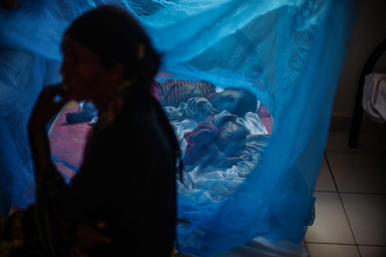 Børn sover under myggenet på Ainabo stabiliseringscenter.