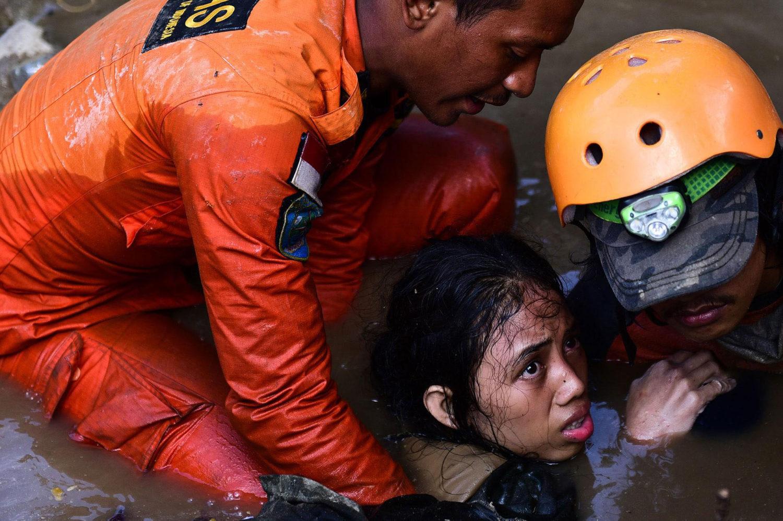 Redningsarbejdere befrier en rædselslagen pige, der har været fanget under murbrokker efter jordskælvene i Indonesien
