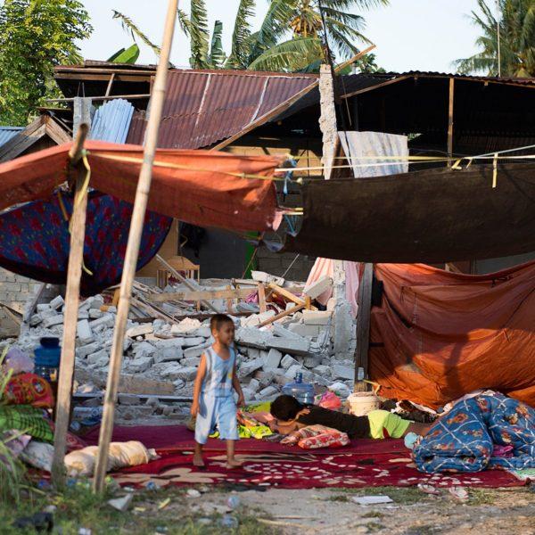 En dreng går udenfor sit ødelagte hus i Palu i den centrale Sulawesi. Huset blev ødelagt da et kraftigt jordskælv og tsunami ramte øen. Hjælp børnene ramt af jordskælv og tsunami i Indonesien. / AFP PHOTO / Bay ISMOYO