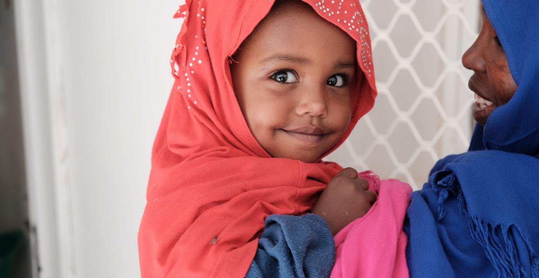 Et billede fra Somalia af en sund, smilende og glad pige med hele verden for sine fødder.