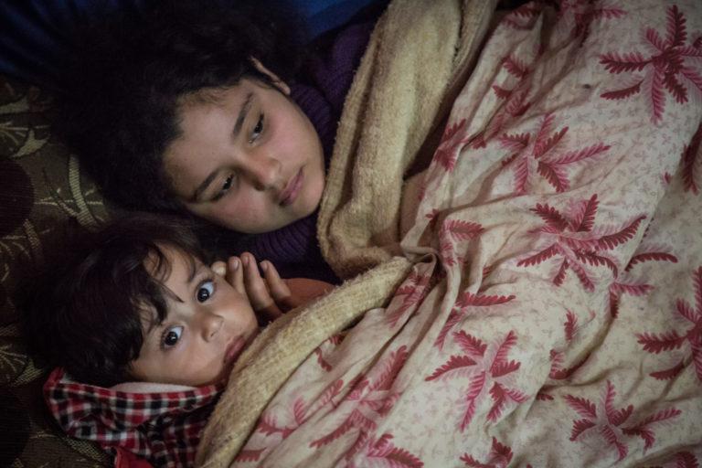 12-årige Hilala varmer sig sammen med sin 1-årige lillebror Hasan. De bor i en flygtningelejr i Libanon, der om vinteren rammes af kulde, sne og tung regn.