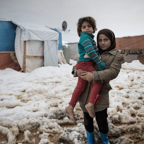 Det er koldt at gå igennem sneen med bare tæer. Thuraya passer på sin søster Rima på tre år og bærer hende igennem sneen, så hun ikke bliver syg af kulde.