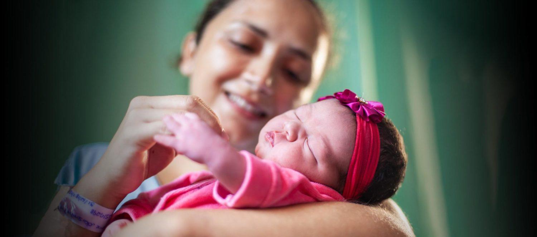 Baby ligger i sin mors arme