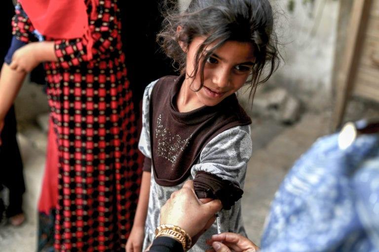 7 årige Wedyan får sin mæslinge vaccine i Tabqa by i Raqqa