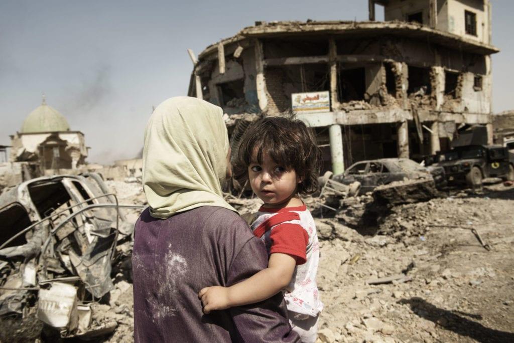 En kvinde bærer sit barn igennem ruiner i Mosul i Irak
