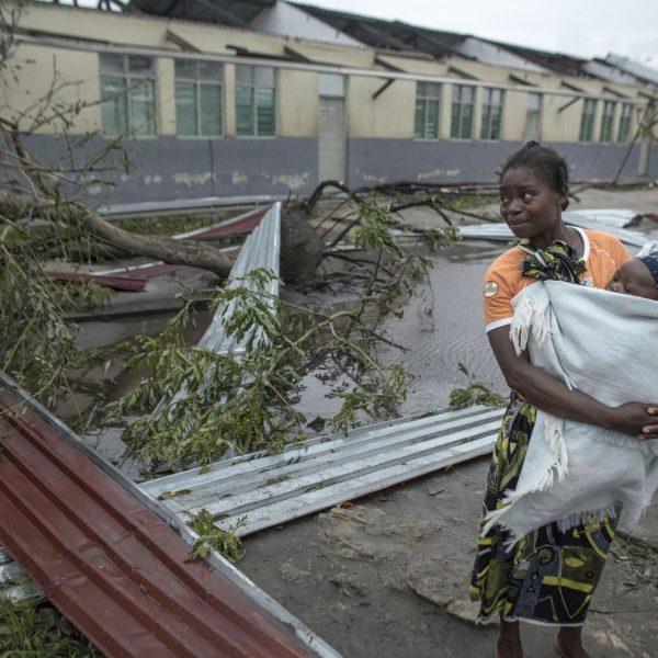 en mor står i ødelæggelserne med sit barn i armene