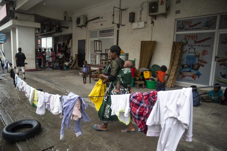 Virginia Fransisco hænger vasketøj op på en improviseret tørresnor på gaden mens hun bærer sin baby Nelson Fransisco på ryggen.
