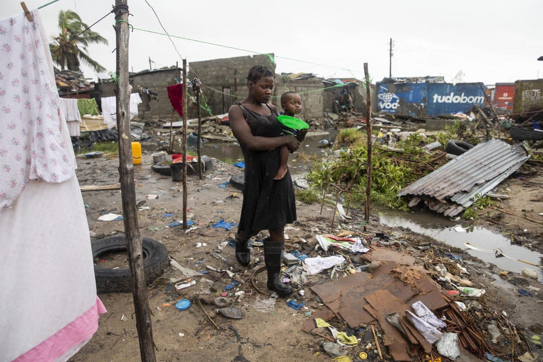 En mor står med sin søn i blandt ødelæggelserne efter cyklonen