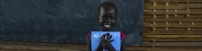 En pige holder sin unicef tekstbog i favnen
