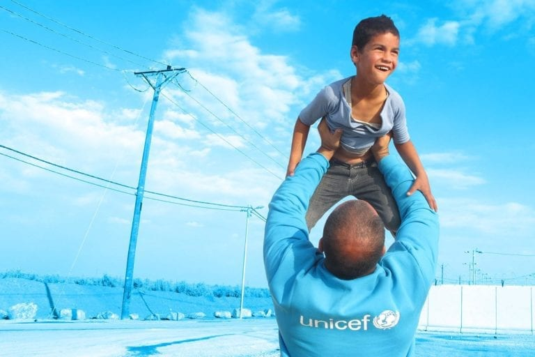 UNICEF medarbejder løfter dreng op