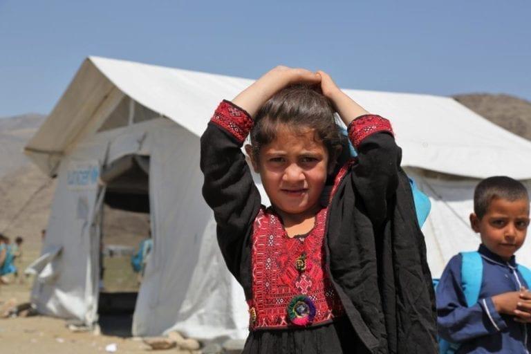En ung pige står foran et telt, der tjener som en fællesskabsbaseret skole i Gamberi-afviklingen for tilbagevendte i Laghman-provinsen, østlige Afghanistan.