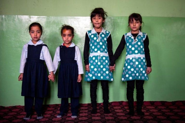 To par tvillingpiger, alle fem år gamle, står foran en malet mur inde i et børnehavecenter i Kabul, Afghanistan.