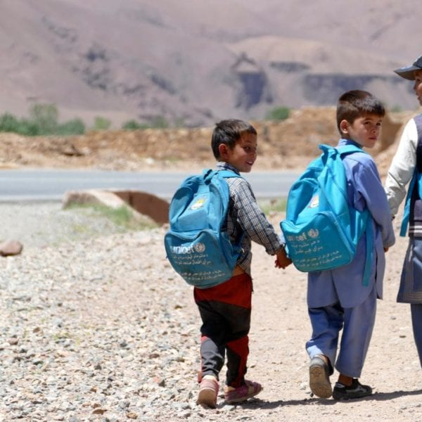 tre drenge i skolealderen er på vej i skole med deres unicef skoletasker på ryggen i afghanistan