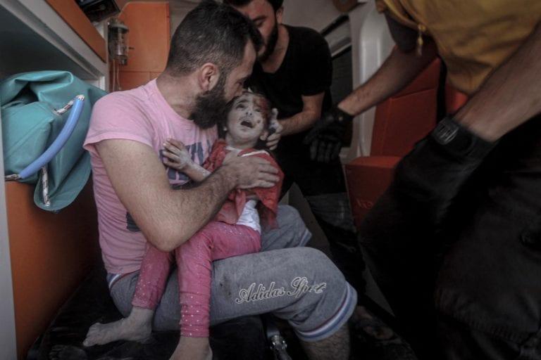 Lille pige modtager hjælp af ambulancefolk efter et luftangreb på markedsplads i Syrien, hvor mindst 11 blev dræbt.