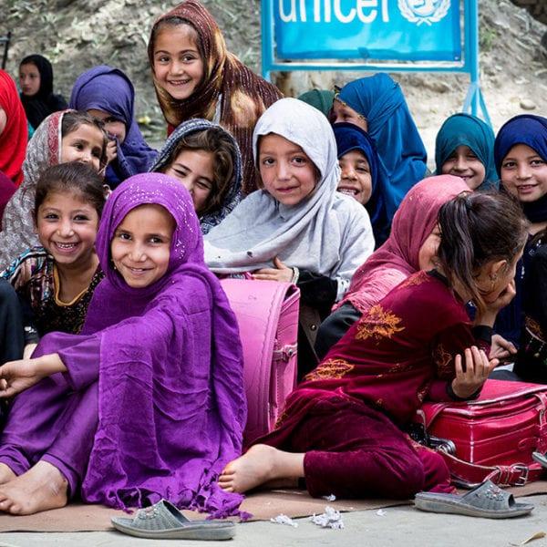Skolepiger sidder foran en midlertidig skole, som UNICEF har etableret efter at pigernes skole blev ødelagt af bomber.