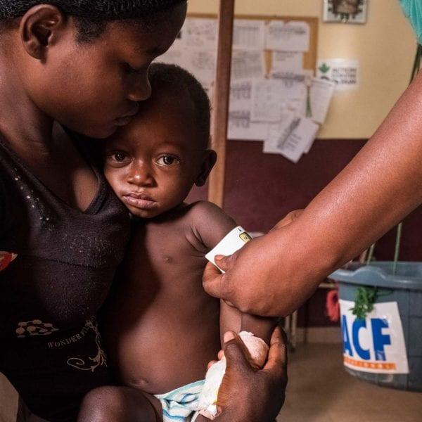 1-årige Martino Bokale bliver målt af en sundhedsarbejder for at se, om han er underernæret.