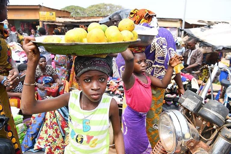 Piger sælger frugt på gaden i Korhogo, Elfenbenskysten. Det er ofte fattigdom, der tvinger børn til at arbejde.