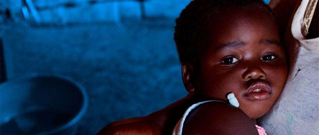 2-årige Shakaira Chitano sidder hos sin mor. Hun har lige fået ordineret medicin imod malaria. Billede i bredt format