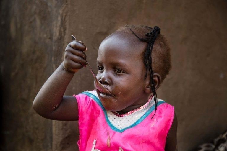 Rumerings søster, 2-årige Grace, spiser grød udenfor deres hjem. Grøden er lavet på forurenet vand.