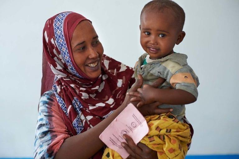 En kvinde holder sit barn på et UNICEF-sundhedscenter i en flygtningelejr i Djibouti. Den lille dreng er lige blevet vaccineret på klinikken og har fået et pink vaccinationskort.