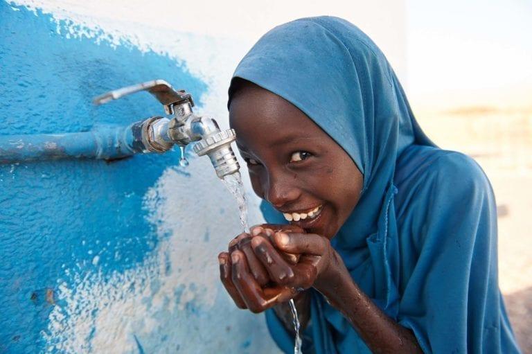 En ung pige drikker renset vand udenfor en UNICEF-støttet skole i Dafo, Djibouti.