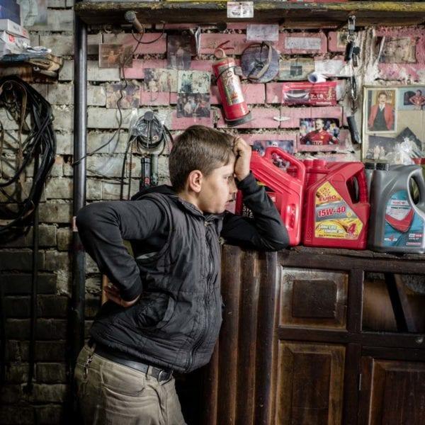 14 årige Mohammed, der en syrisk flygtning fra Kobani, læner sig op af en kommode.