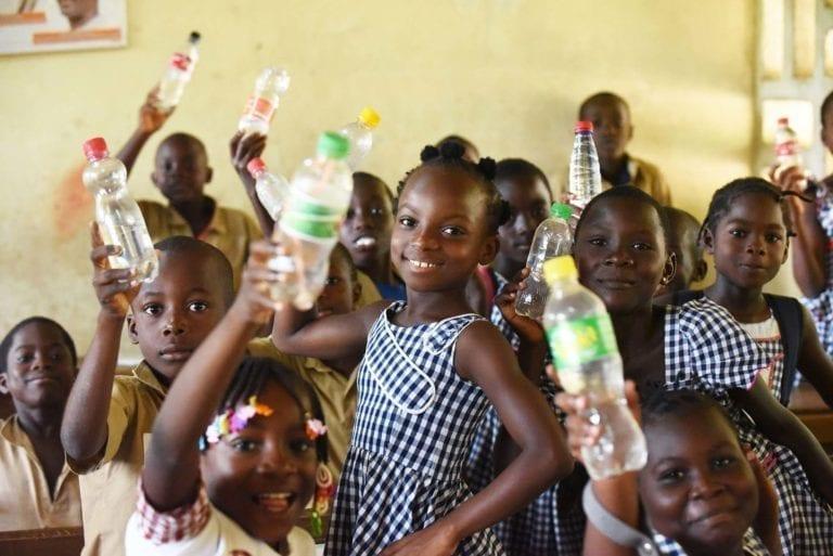 Børn fra en skole i Adjake, Elfenbenskysten, viser deres vandflasker frem. De går på en af de skoler, hvor UNICEF har fået etableret vand og sanitetsforhold.
