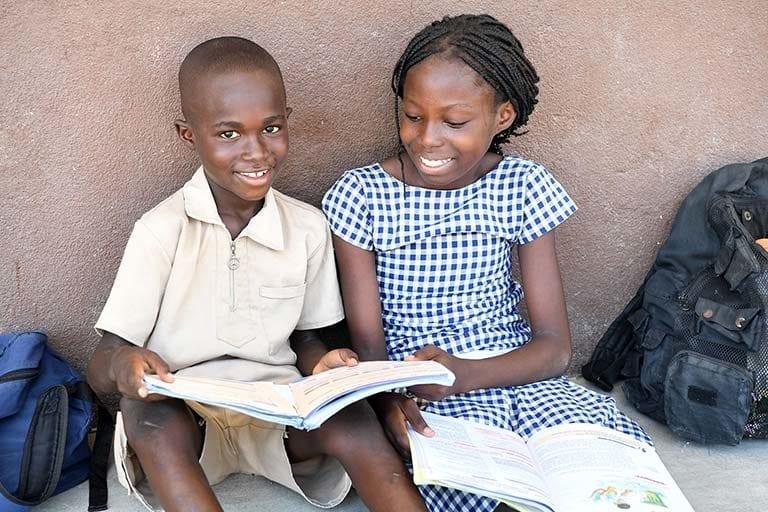 Elever foran en skole i Elfenbenskysten. UNICEF støtter Uddannelsesministeriet i Elfenbenskysten med at opbygge nye skoler og uddanne skolelærere.