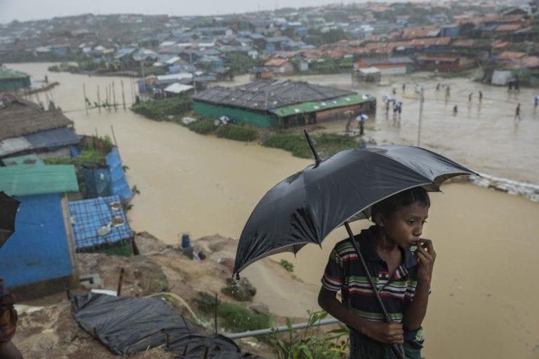 En dreng holder en paraply, mens man kan se lejren i Cox's Bazar Bangladesh