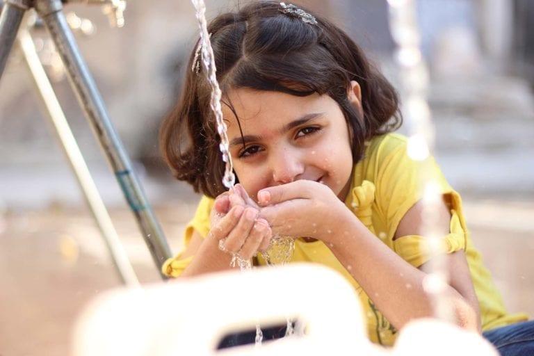 8-årige Huda henter vand fra en UNICEF-støttet vandtank i Aleppo, Syrien.