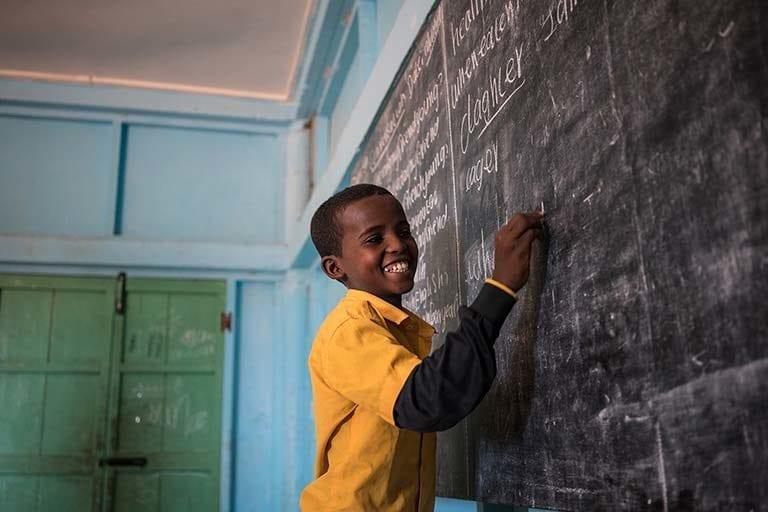 En dreng skriver på tavlen i sit klasseværelse på en UNICEF-støttet skole i Somalia.