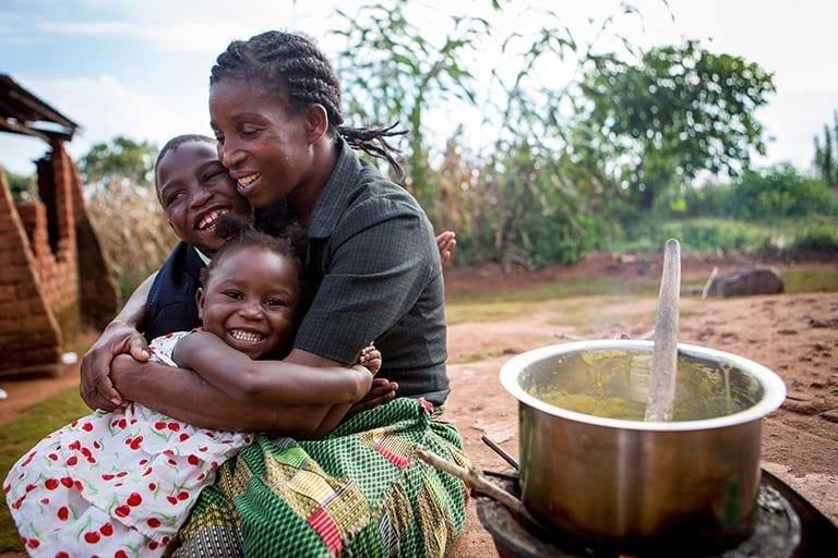 Maria sidder med sine to børn i deres hjem i landsbyen Gunde i Malawi. Maria er hiv-positiv, men fordi hun kom i behandling i tide, er hendes to børn ikke smittet med sygdommen. Siden 2001 er antallet af nye hiv-infektioner blandt små børn faldet med 58%,