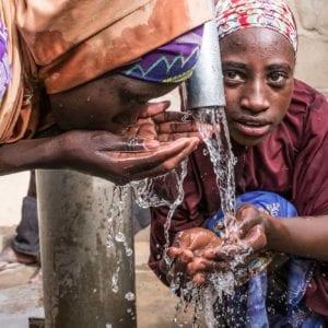 To nigerianske piger drikker rent vand i en flygtningelejr i Chad.