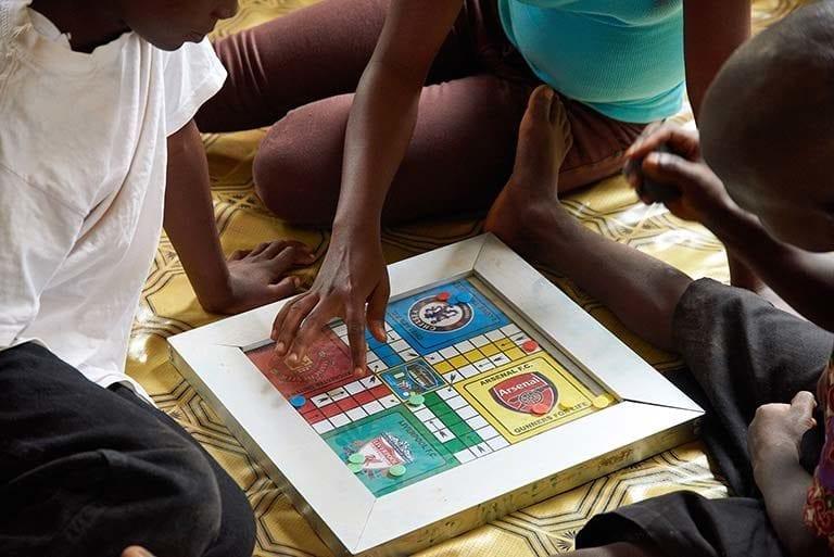 Børn spiller et brætspil hos den UNICEF-støttede organisation HAPPY kids and Adolescents i Sierra Leone.