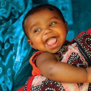 En sød smilende dreng bæres af sin mor