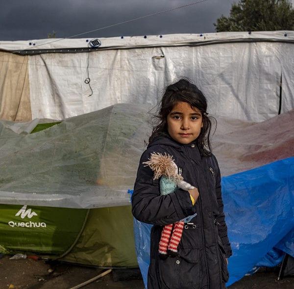 En flygtningepige står foran sit telt i modtagecenteret Moria i Grækenland