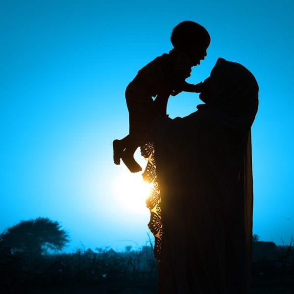 Halim fra Tchad løfter sit lille barn.