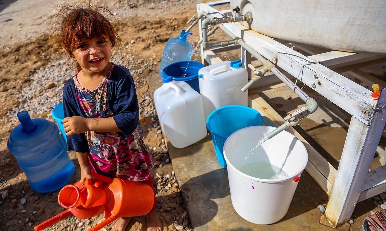 3-årige Sahira henter rent vand fra en UNICEF-vandtank