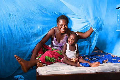 Elfenbenskysten sover under et beskyttende myggenet sammen med sin mand og deres børn, så de ikke bliver smittet med malaria.